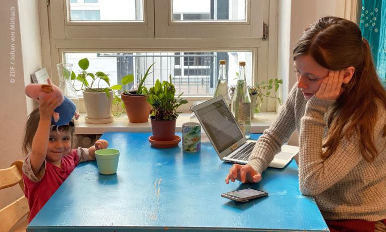"""ZDFzeit: Filmstill aus """"Nichts mehr wie früher (© ZDF / Johan von Mirbach): Foto einer Frau mit Kleinkind am Küchentisch, vor ihr Laptop und Handy"""