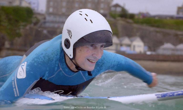 """Filmstill aus """"Chicks on Boards"""": Frau paddelt auf Board (© Labo M.)"""
