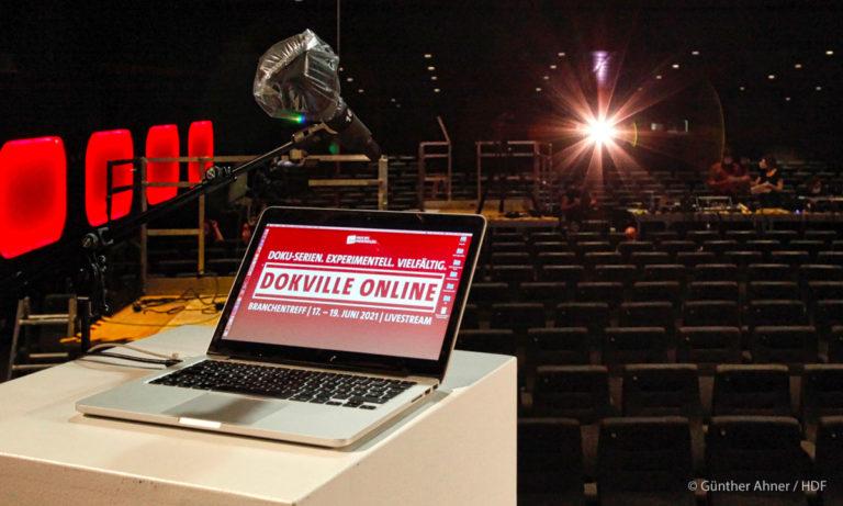 Bühnenansitz von DOKVILLE 2021 online mit Blick ins Kino. Man sieht einen Rechner und ein Mikro mit Plastikschutz (Foto: Günther Ahner / HDF)